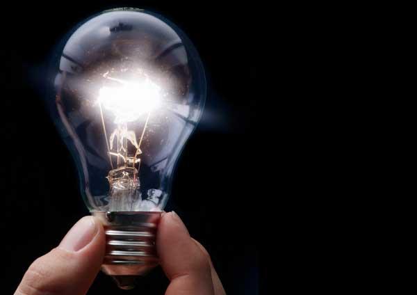 Ampoule allumée, tenu par une personne depuis le culot.
