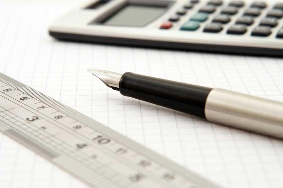 Gros plan sur une scene de bureau technique, on y voit un morceau de règle, un stylo plume et en arrière plan une calculatrice